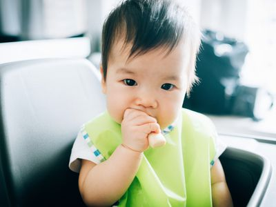Adorable baby eating baby finger biscuit on high chair - stock photo
