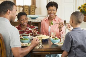 Family eating dinner together, talking and smiling
