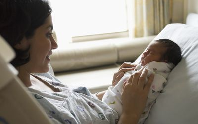 Mother holding newborn baby in hospital