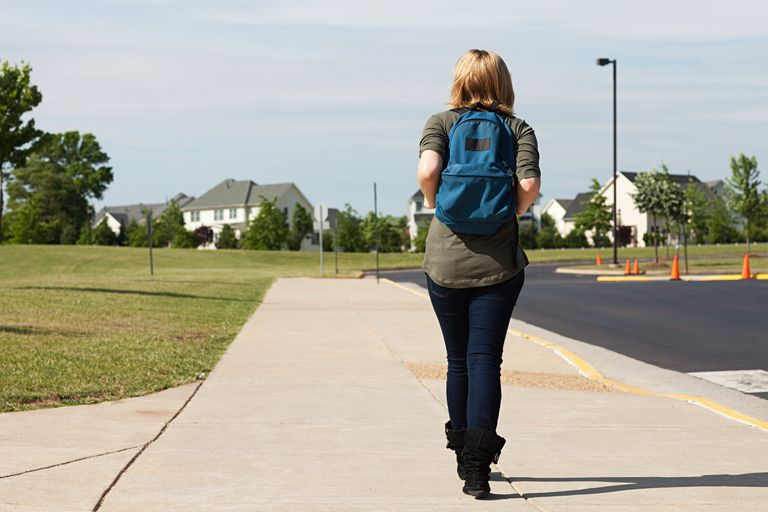 A young teen girl walking away from school.