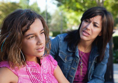 concerned mother talking to tween girl