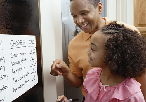 A daughter and father looking at a behavior chart
