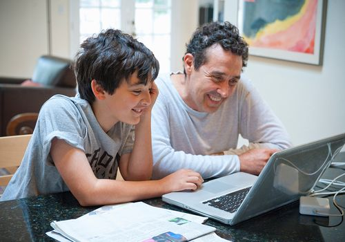 father and tween son share laptop on kitchen counter