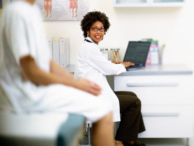 Female doctor talking to patient and using laptop in exam room, discussing IUI procedure