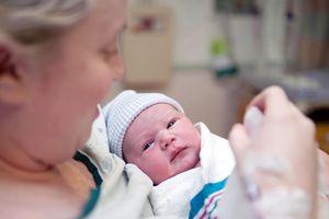 Mother cradling newborn baby girl