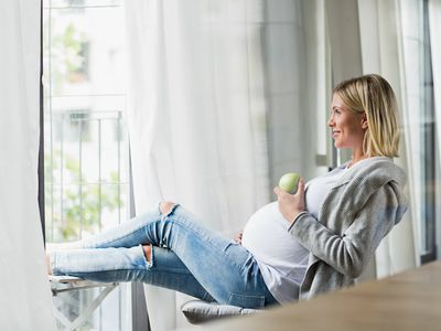 Woman sitting in chair eating green apple