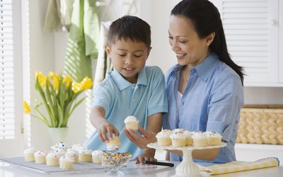 Asian mother and son decorating cupcakes