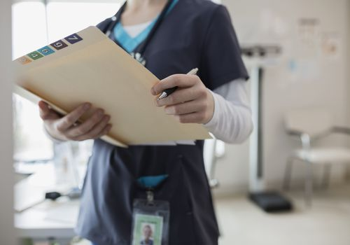 Nurse in scrubs holding medical chart in clinic