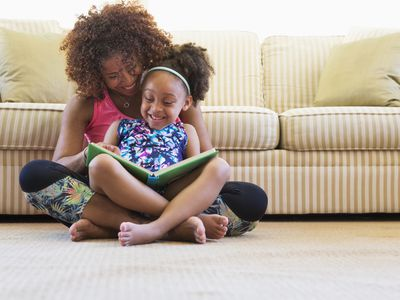 BIPOC mom and daughter reading