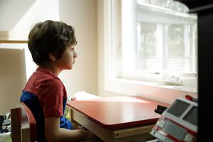 A boy with brown hair and a red shirt sits at a brown desk sadly looking out the window.