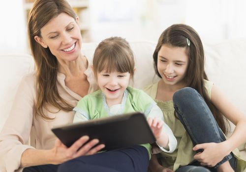 Mother and daughters (4-5,8-9) using tablet pc, Jersey City, New Jersey, USA