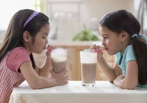 Young girls drinking chocolate milk together