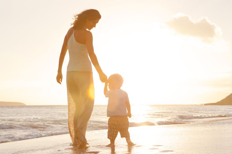 Woman in her 40s walking on beach with a child, getting pregnant after 35 is harder but not impossible