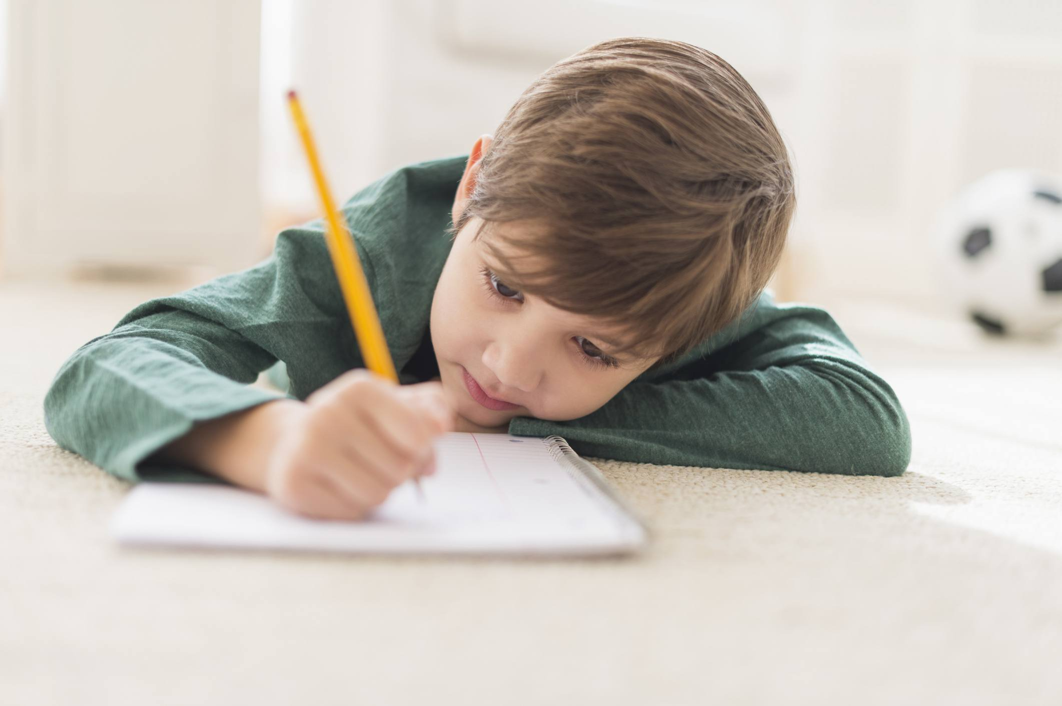 Little boy writing in a notebook on the floor
