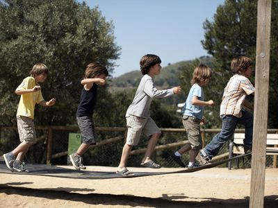 Six boys jump on playground structure.