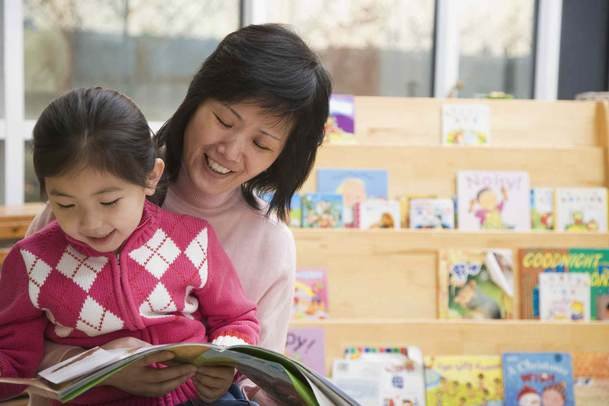 Girl (4-5 years old) sitting on teacher's lap reading a book