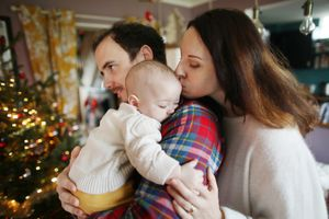 A 6 months old baby in the arms of his parents at home, in a Christmas atmosphere