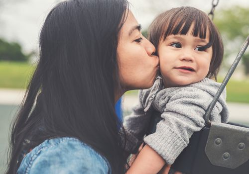 Mom kissing toddler at the playground