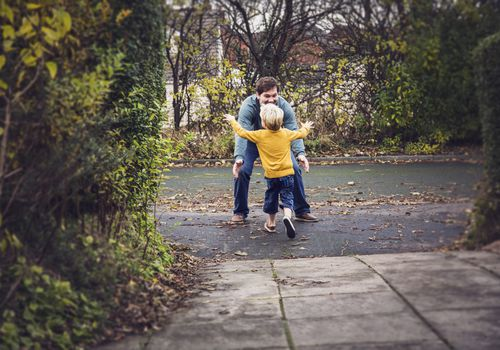 A little boy running into his father's arms outdoors