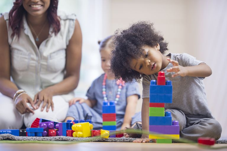 toddler boy playing with building blocks while mom and sister watch