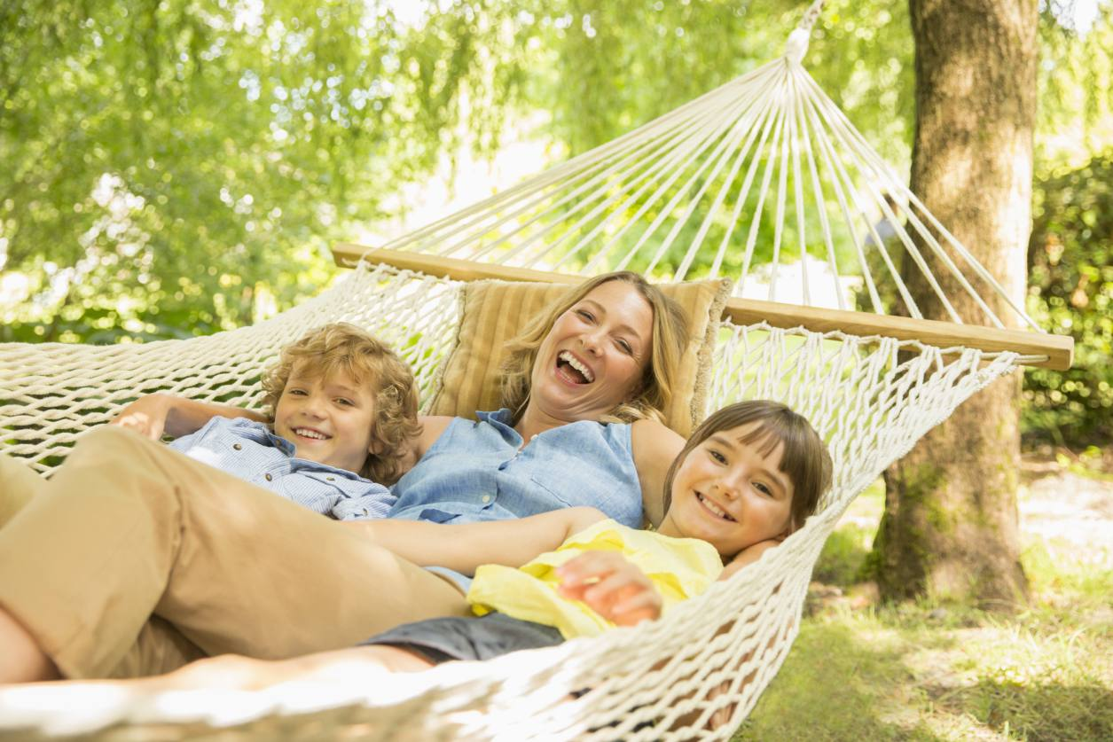 Mom and two kids laughing in hammock