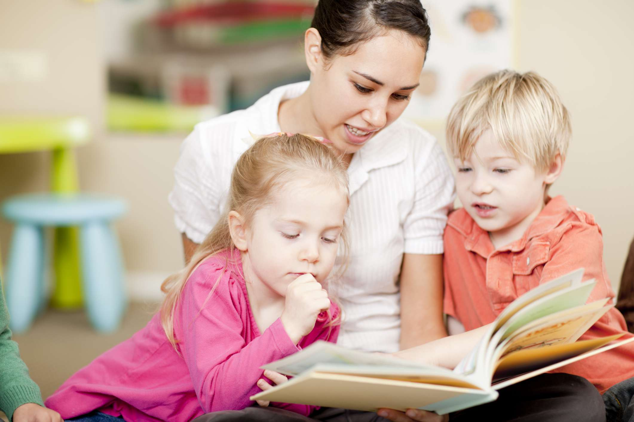 Childcare worker reading to two children