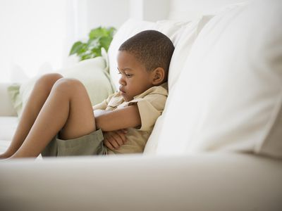 a boy sitting on a sofa having a time out