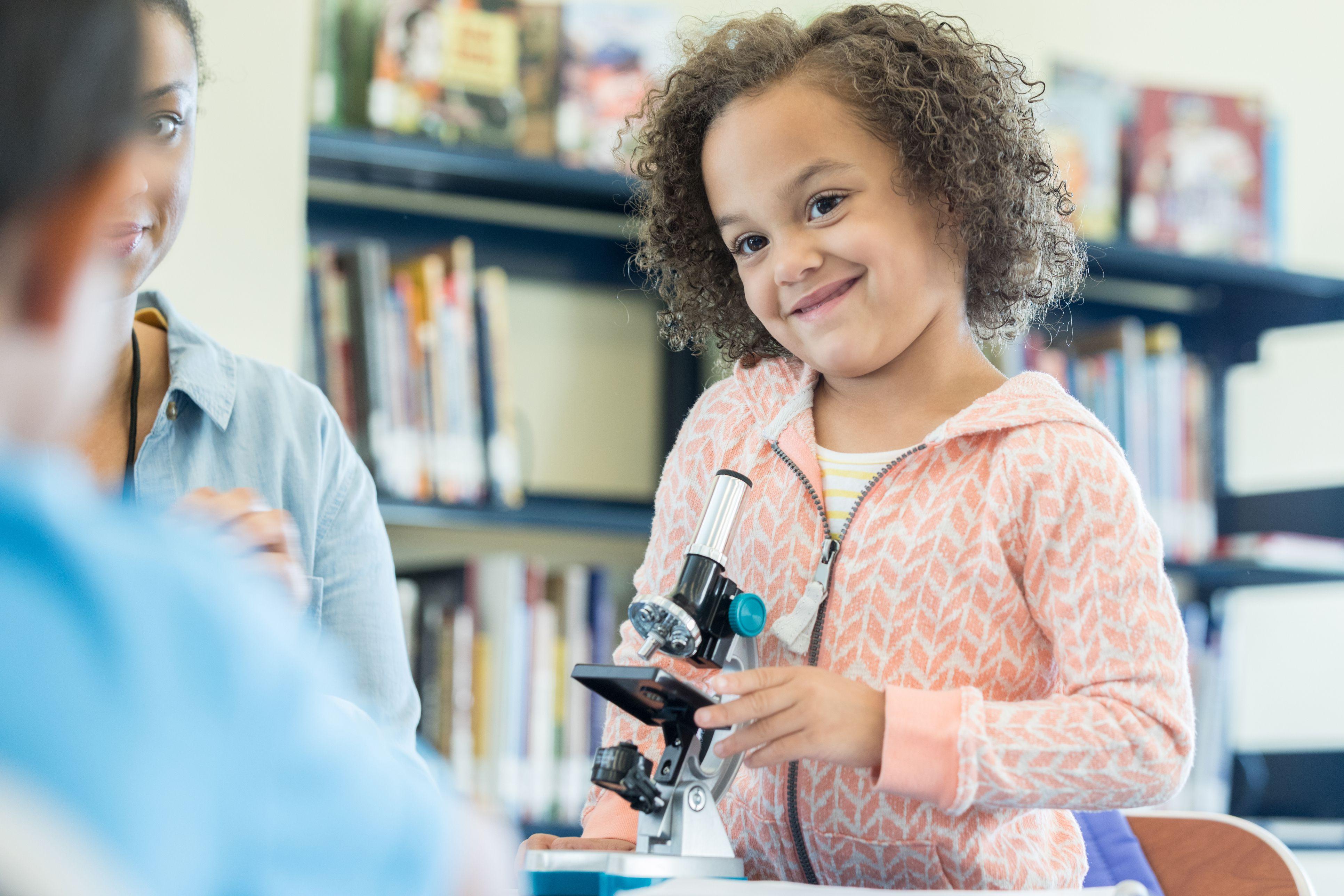 Adorable little girl using microscope
