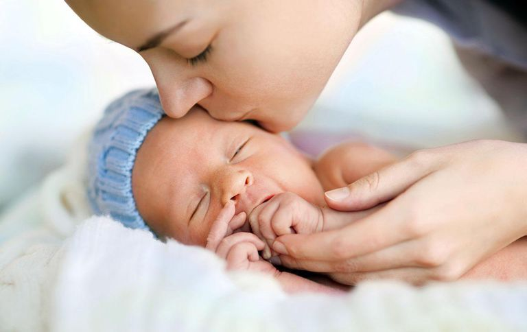 Close up of sleeping newborn and kissing mother