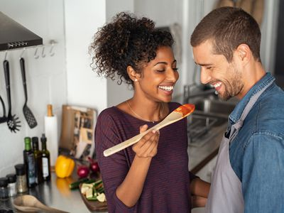 Multiethnic couple tasting fertility-boosting food from wooden spoon