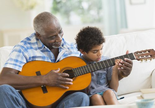 Boy playing guitar with grandfather on couch