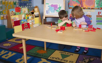 Boy and a girl playing at a preschool table