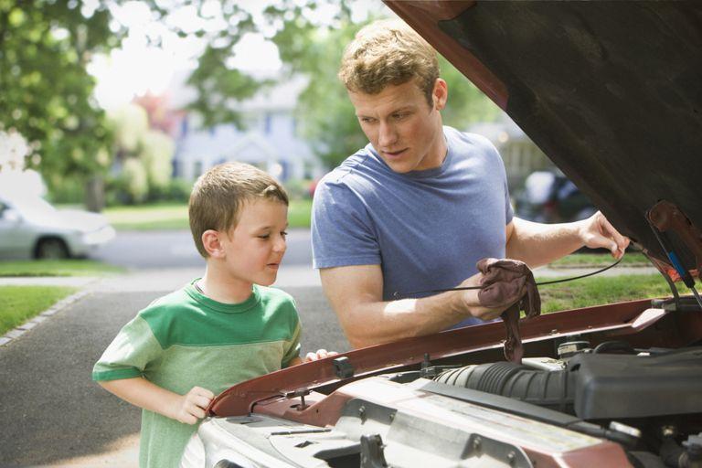 boy watching father repair car