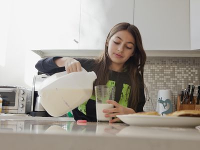 Young girl pouring a glass of milk in a kitchen