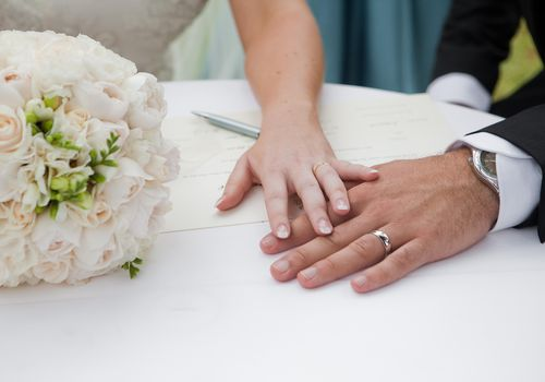Bride and groom's hands touching on table