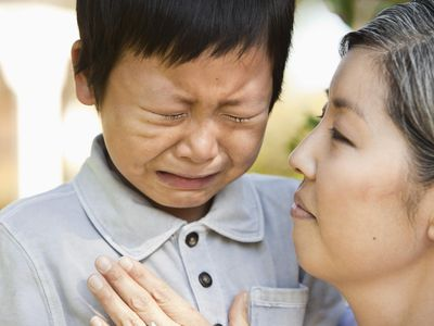 Asian mother comforting crying son