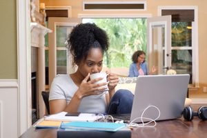 Student studying at home with parent in the background