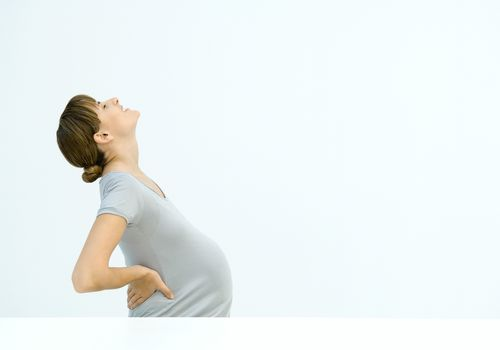 A pregnant woman bending backward, seen from the side.