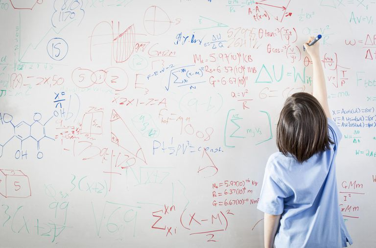 Schoolgirl writing on a dry erase board full of math equations