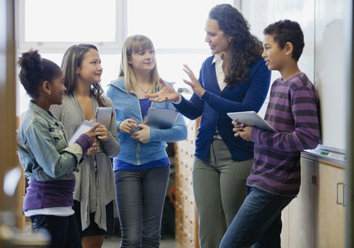 Middle school students talking with teacher in classroom