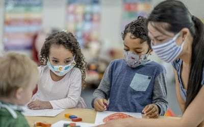 Kids coloring while wearing masks in school