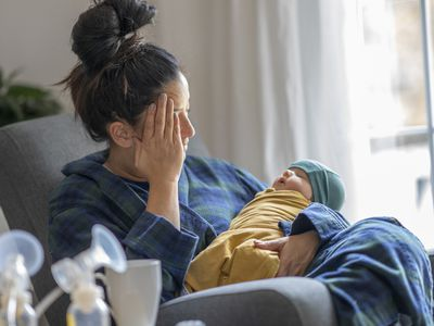 Tired new mother holding her baby - Stock Image
