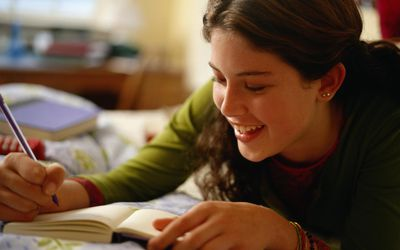 Teenage girl writing in a journal
