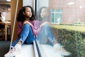 Young girl sitting on window ledge
