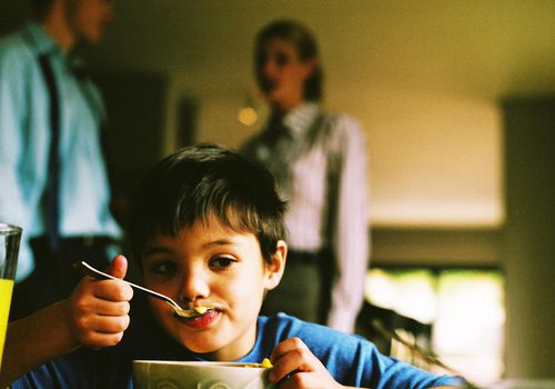 Close-up of a young boy (8-10) eating a bowl of cereal with parents standing in the background.