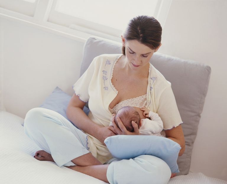 Woman breastfeeding baby in football position or clutch hold.