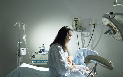 Pregnant woman sitting on pregnancy bed in hospital