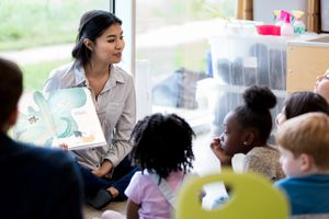 Librarian reads children a book during story time