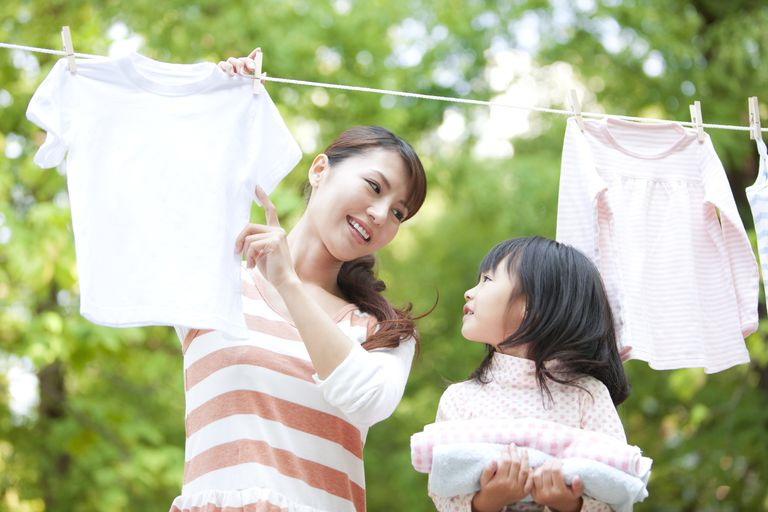 5 year old child development - girl helping mother with laundry