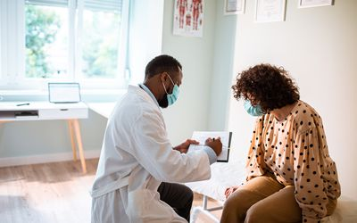 A doctor shows a patient notes in an examination room.